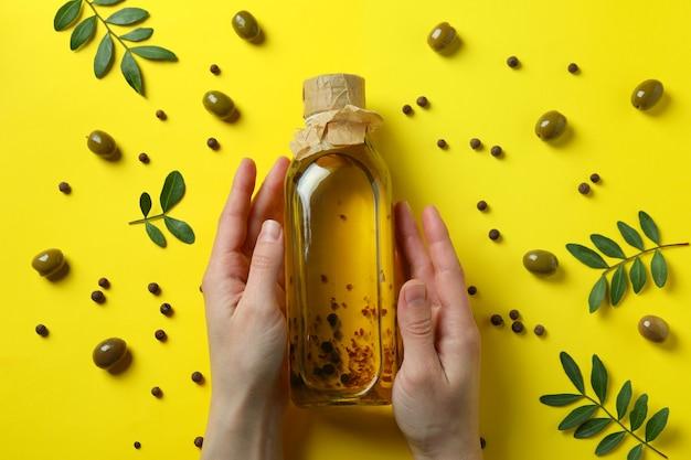 Женские руки держат бутылку оливкового масла на желтом