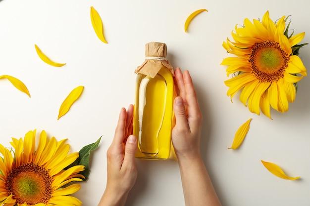 Женские руки держат бутылку подсолнечного масла