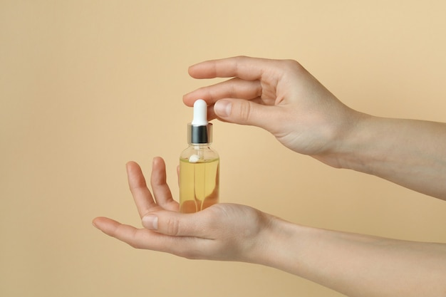 Female hands hold bottle with pine oil on beige