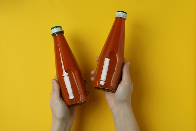 女性の手は黄色の孤立した背景にニンジンジュースのボトルを保持します。