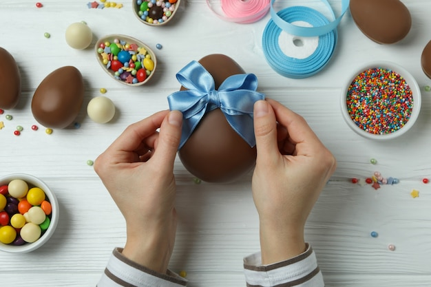 Female hands hold bow on chocolate egg on white wooden with easter accessories