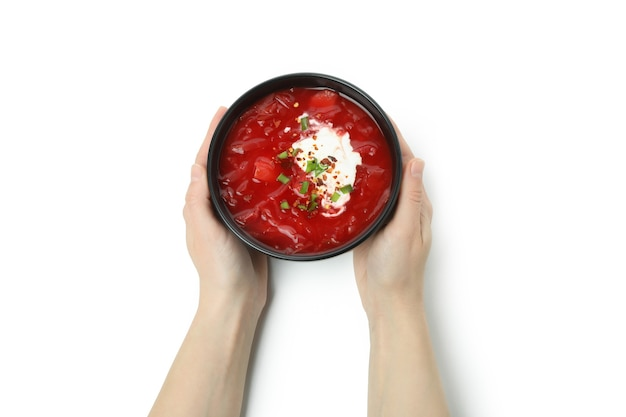 Female hands hold bowl of borscht, isolated on white