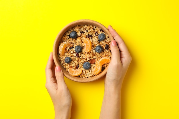 Female hands hold bowl with granola on yellow background, top view