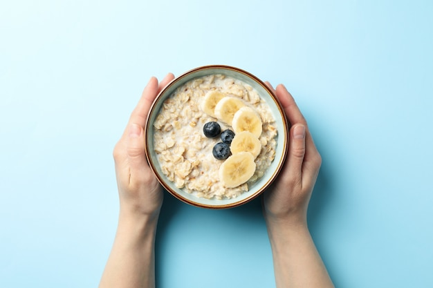 Female hands hold bowl with oatmeal porridge and fruits on blue wall