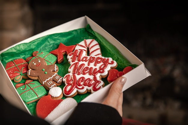 Female hands hold a box with beautiful festive craft christmas cookies on a blurred dark background. happy new year concept.