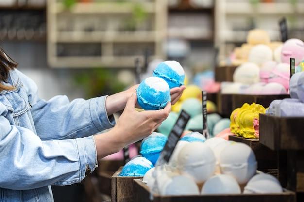 여성의 손은 화장품 가게에서 밝은 목욕 폭탄을 보유하고 있습니다. 바디 케어 개념.
