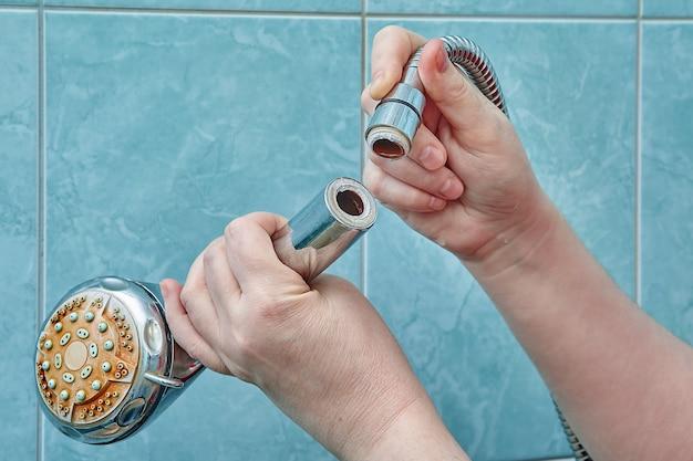 Female hands hold broken shower head in bathroom with blue tiles.