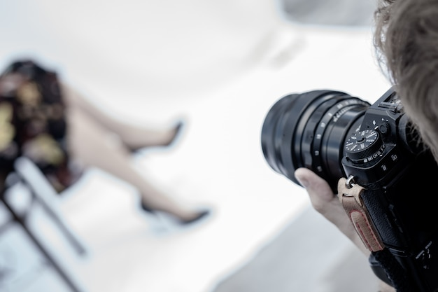 Female hands hold the camera. the model is posing.