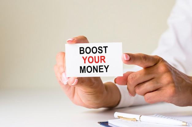 Female hands hold card paper with text boost your money on a white light background. business and finance concept. how do you want the accounts handled