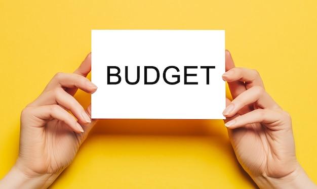 Женские руки держат бумагу карточки с текстом бюджета на желтом фоне. концепция бизнеса и финансов