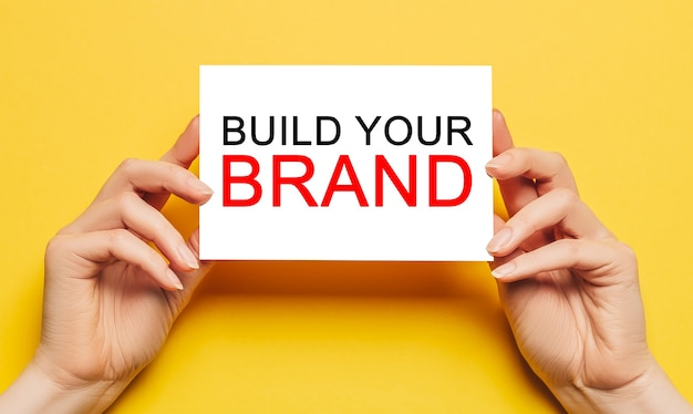 여성의 손에 노란색 배경에 텍스트 빌드 귀하의 브랜드와 카드 용지를 잡아. 비즈니스 개념