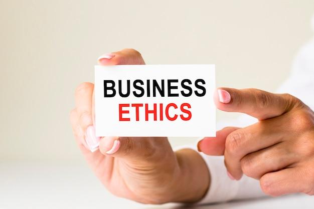 여성의 손은 흰색 배경에 텍스트 비즈니스 윤리가 포함된 카드 용지를 들고 있습니다. 비즈니스 및 금융 개념