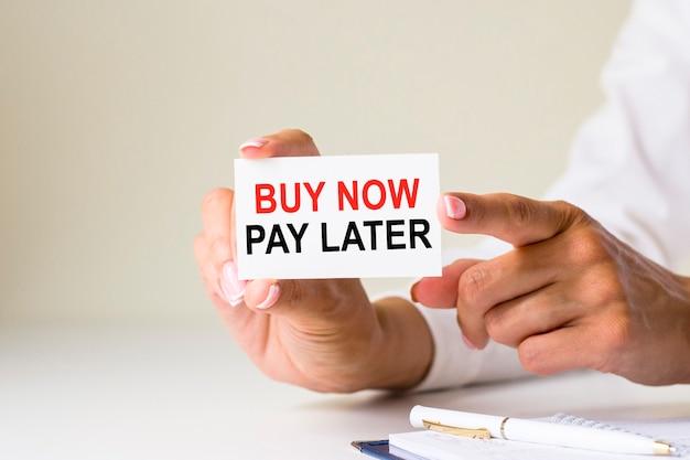 여성 손은 흰색 배경에 buy now pay later라는 텍스트가 있는 카드 용지를 들고 있습니다. 비즈니스 및 금융 개념입니다. 계정을 어떻게 처리하시겠습니까?