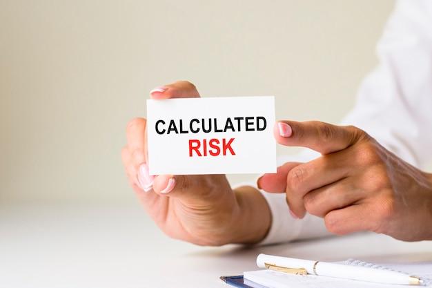 女性の手は、白色光の背景にリスクを計算したテキストでカード紙を保持します。ビジネスと金融の概念。アカウントをどのように処理しますか