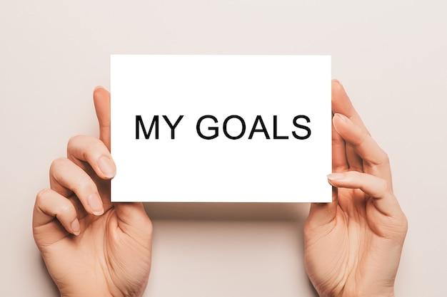 女性の手は黄色の背景にテキスト私の目標とカード紙を保持します。ビジネスと金融の概念