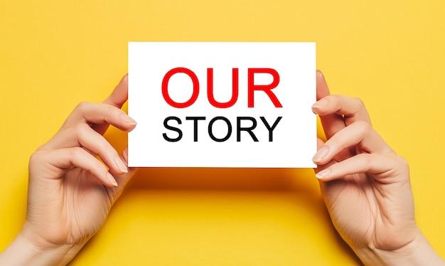 女性の手は黄色のスペースにテキスト私たちの物語とカード紙を保持します