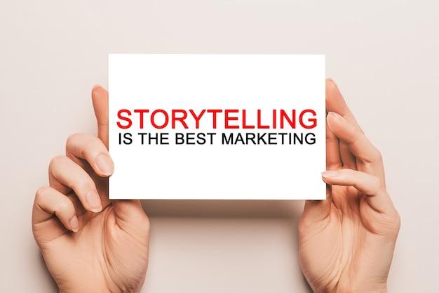 女性の手はテキスト付きのカード紙を持っていますストーリーテリングは黄色い空間で最高のマーケティングです