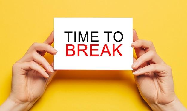 女性の手は、黄色の背景に「timetobreak」というテキストが書かれたカード用紙を持っています。ビジネスと金融の概念