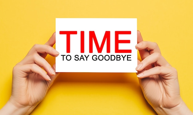 女性の手は、黄色の表面に別れを告げるテキストの時間でカードを保持します。ビジネス、金融の概念