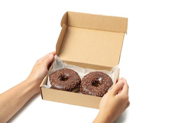 Женские руки держат картонную коробку с пончиками, изолированными на белом