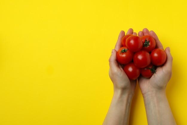 여성의 손을 잡고 노란색 바탕에 체리 토마토