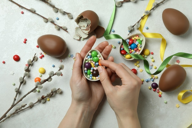 Female hands hold chocolate egg on white textured wall with easter accessories