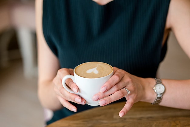 Female hands hold coffee