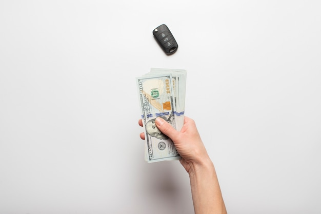 Female hands hold, counts money, dollars on a light background with a car key. concept of pay, purchase, taxes, rent, leasing.