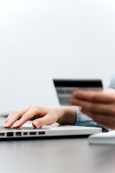 Female hands hold credit card, pressing buttons and making online purchase closeup.
