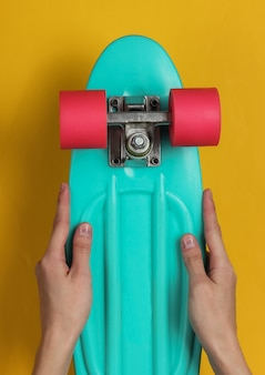 Female hands hold cruiser board on yellow paper