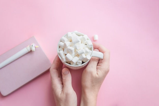 Female hands hold a cup of coffee with marshmallows with a notepad and a unicorn pen. autumn or winter concept. flat lay, top view