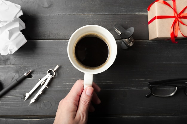 A female hands hold a cup of coffee on the wood table