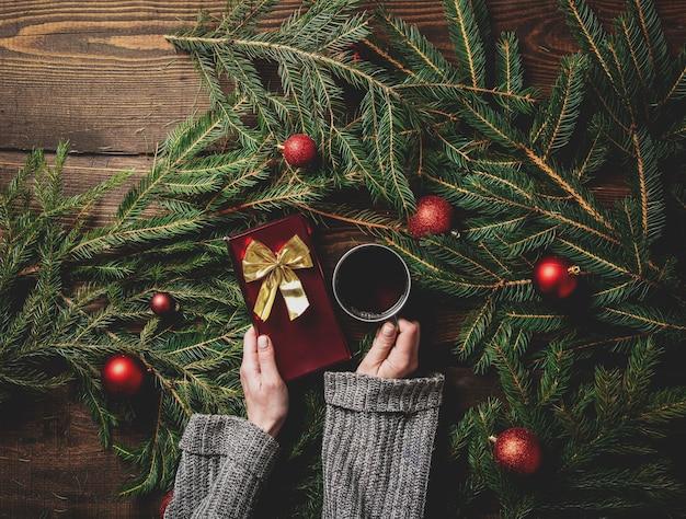Женские руки держат чашку чая и подарочную коробку с елкой на столе