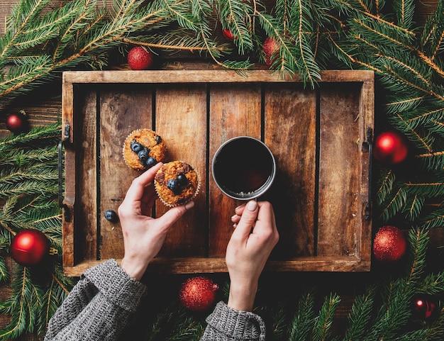 女性の手はテーブルの上のクリスマスツリーとマフィンの横にお茶を持っています