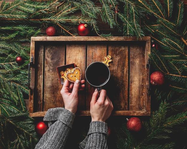 Женские руки держат чашку чая рядом с печеньем и елкой на подносе