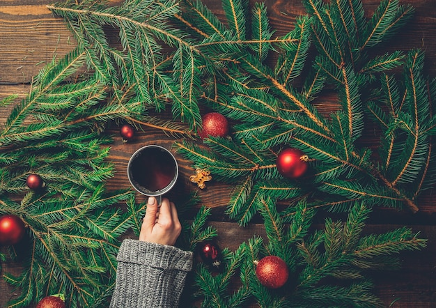 女性の手はテーブルの上にクリスマスツリーとお茶を保持します。