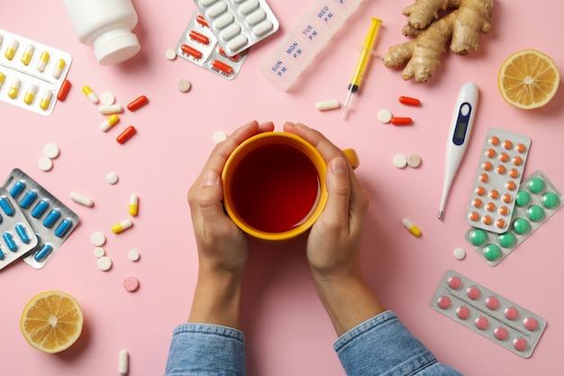 女性の手は、さまざまな薬とお茶のカップを保持します