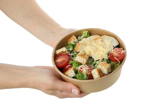 Женские руки держат миску с салатом цезарь, изолированную на белом