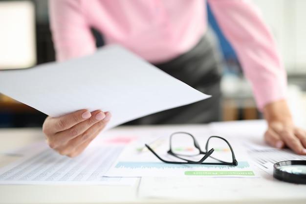Женские руки держат документы на столе, коммерческие диаграммы и увеличительное стекло маленькое и