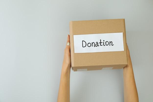 Женские руки держат ящик для пожертвований на светло-сером фоне