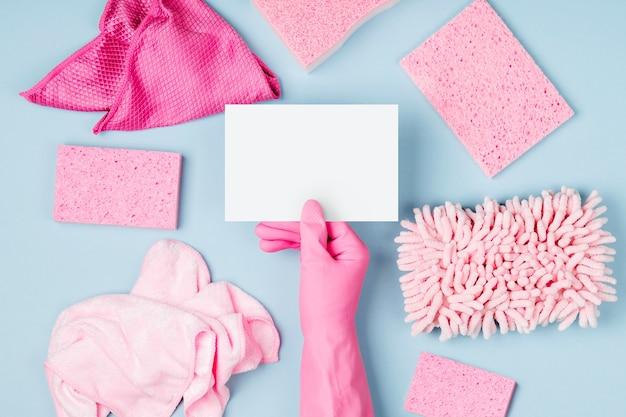 女性の手は洗剤とクリーニングアクセサリーで空のカードの青い背景を保持します
