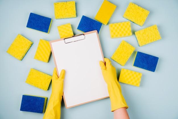 여성 손은 노란색 스폰지가 있는 파란색 배경의 빈 카드를 들고 청소 또는 가사