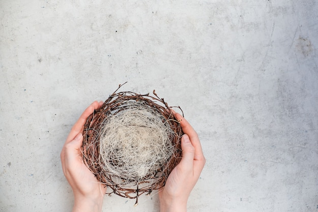 Female hands hold an empty nest with easter colorful eggs. top horizontal view abstract composition. abstract background