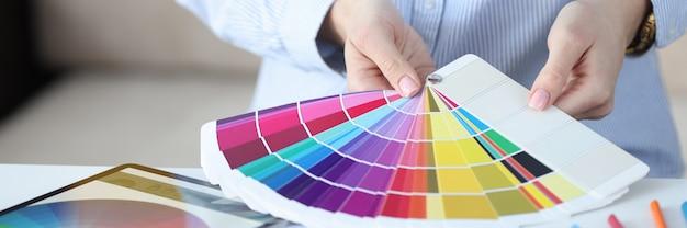 女性の手は、色の選択の概念でカラーパレットデザイナーサービスのファンを保持します