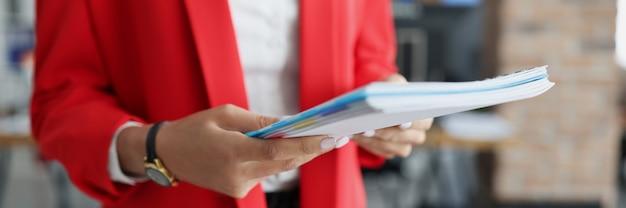 女性の手は財務書類のフォルダーを保持します