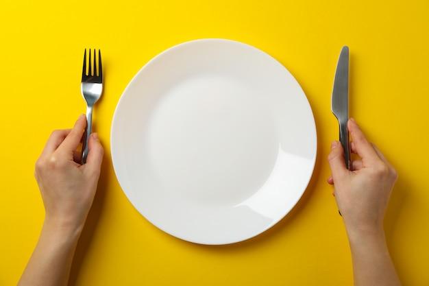 女性の手は、プレート、トップビューで黄色の背景にフォークとナイフを保持します。