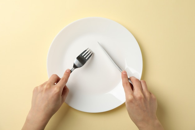 Female hands hold fork and knife on beige background with plate, top view