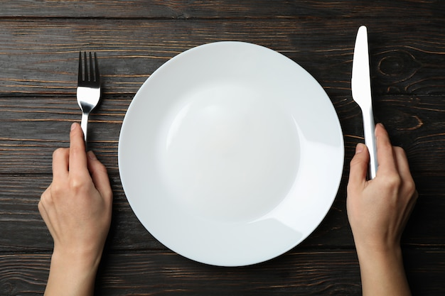 Female hands hold fork and knife on wooden with plate, top view