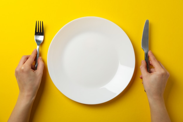 Female hands hold fork and knife on yellow background with plate, top view