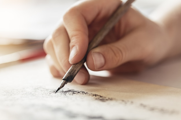 Female hands hold fountain pen for drawing, creative exercises.